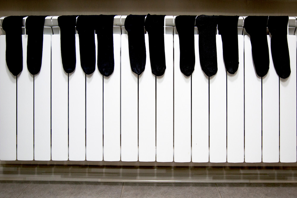 Illustrative image showing black men socks arranged on a heater like a piano keyboard